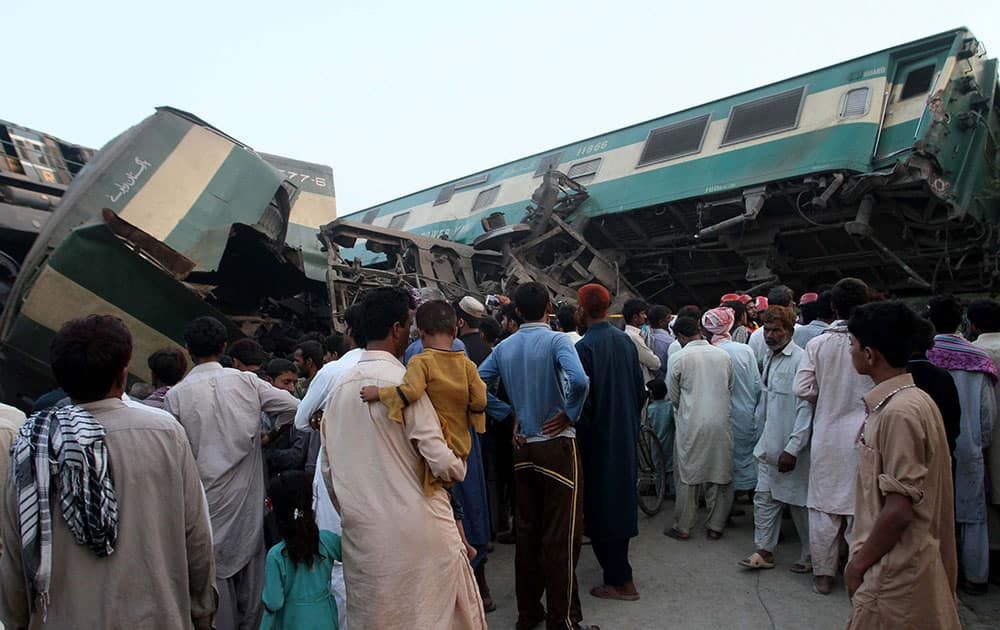 People look at a mangled passenger train that had collided with freight train near Multan, Pakistan