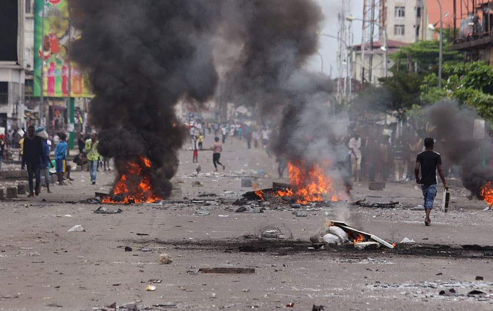 People walk near burning debris during election protests in Kinshasa