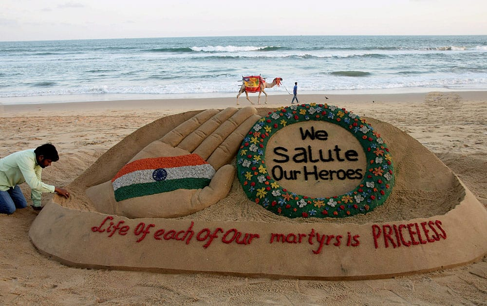 Sand artist Sudarsan Pattnaik creates a sand sculpture on the soldiers who lost their lives in Kashmir with message We salute our Heroes, Life of each of our martyrs is Priceless