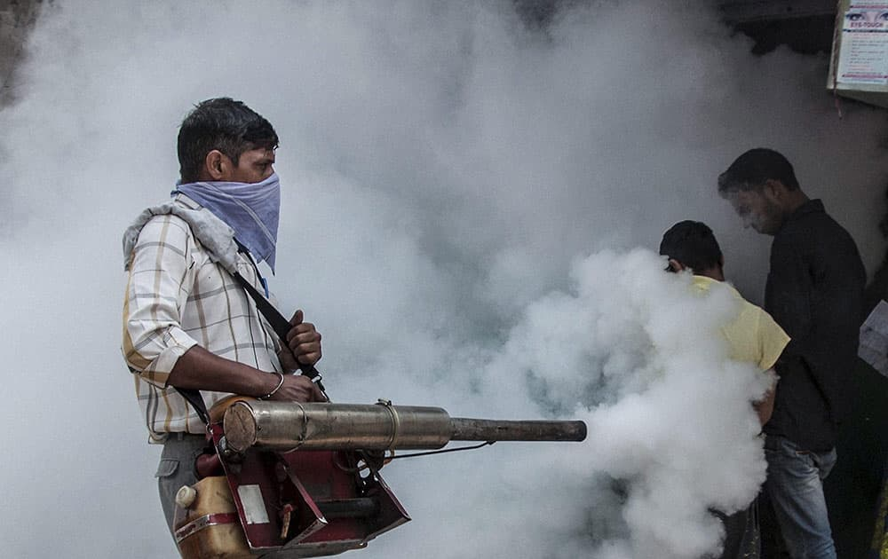 A Municipal Corporation of Delhi (MCD) employee fumigates near Hindu Rao Hospital in New Delhi in the view of mosquito-borne diseases