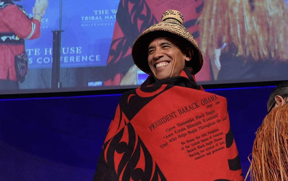 President Barack Obama smiles as he wears a blanket