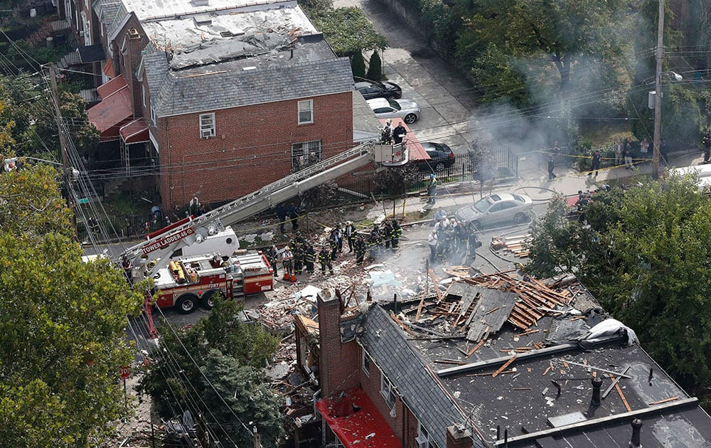 Emergency service personnel work at the scene of a house explosion, in the Bronx borough