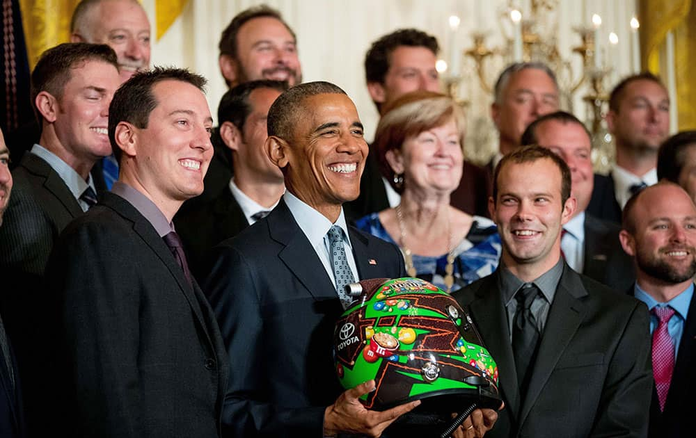 President Barack Obama holds a race car helmet and poses for a photograph with NASCAR race car driver Kyle Busch, left, and members of the Joe Gibbs Racing team