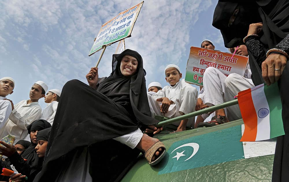 A Muslim girl puts her shoe on Pakistani flag over a tank that was brought after Indo-Pak war in 1971, during a rally in support of Indian army