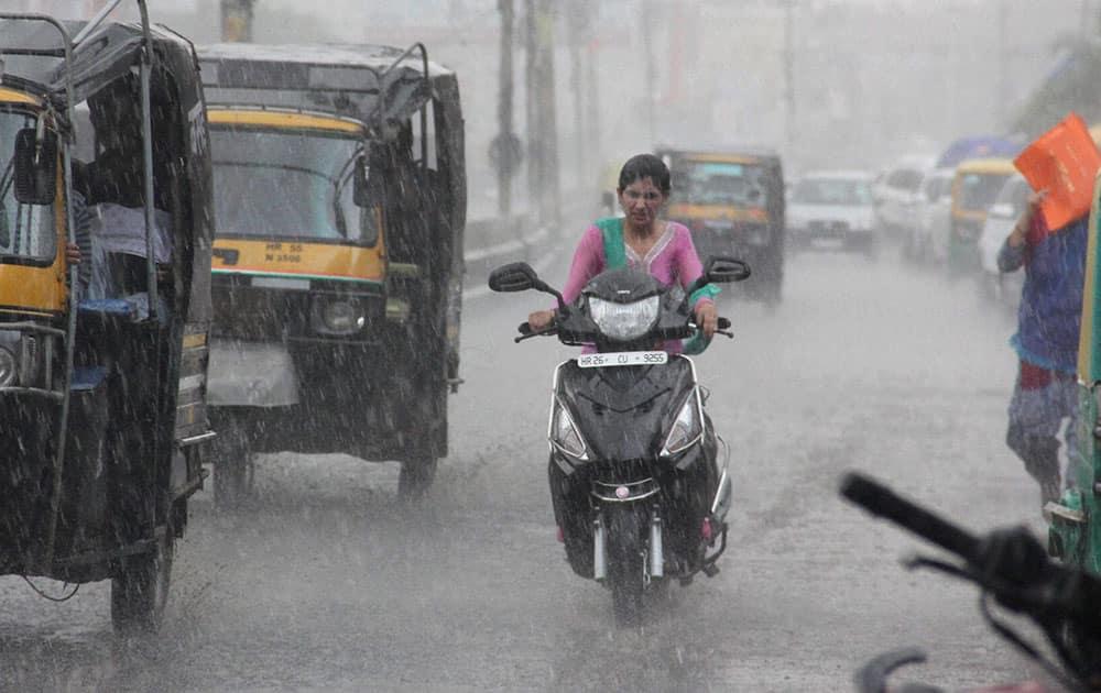 A woman drives in heavy rains in Gurgaon