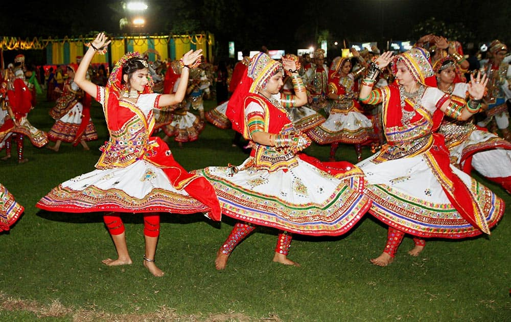 Participants dressed in traditional attire perform Garba