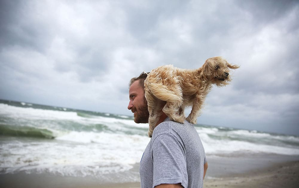 Ted Houston and his dog Kermit visit the beach as Hurricane Matthew approaches the area in Palm Beach, United States