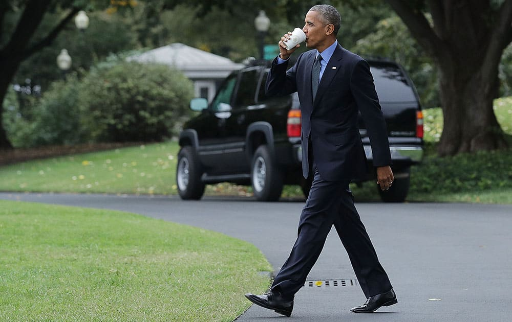 US President Barack Obama takes a sip of tea as he walks across the South Lawn