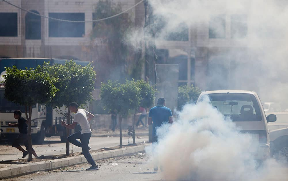 Palestinians run away from teargas as Israeli border police unit raided the family home of the Palestinian gunman who killed two and wounded several other people in Jerusalem earlier in the day, in the West Bank town of al Ram, north of Jerusalem