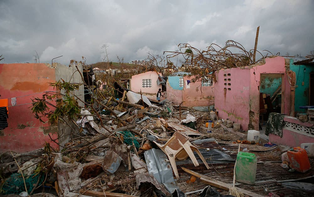 A resident walks amidst damaged buildings and debris in a seaside fishing neighborhood almost completely destroyed by Hurricane Matthew, in Port Salut