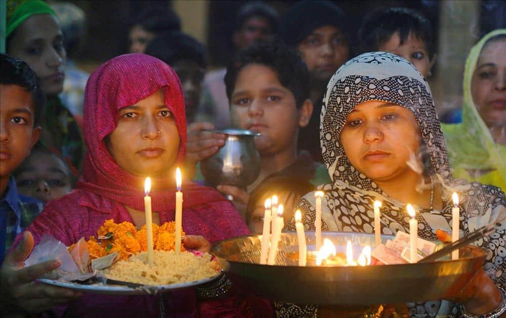 Muslim Woman lighting lamp during Mehndi night before Muharram