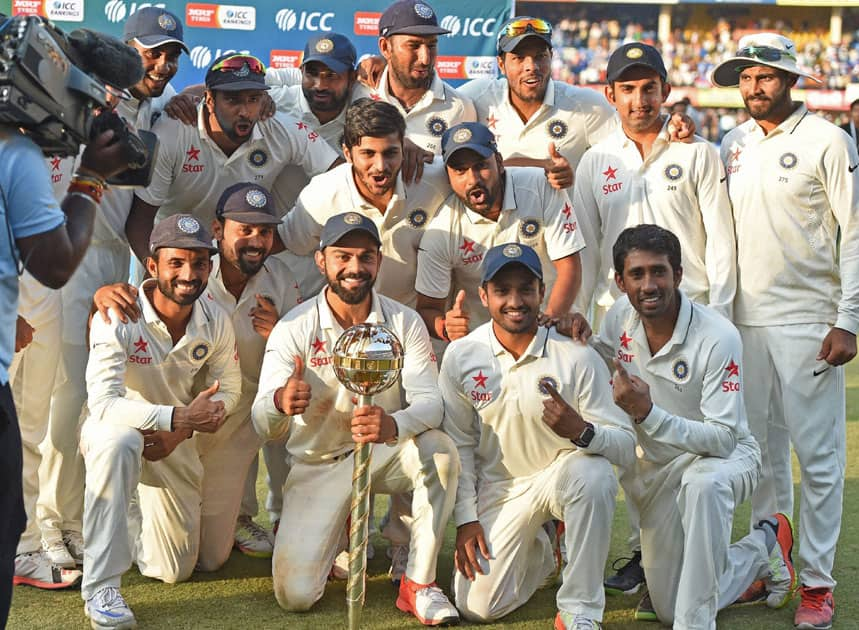 Indian team players pose for a photo with ICC trophy