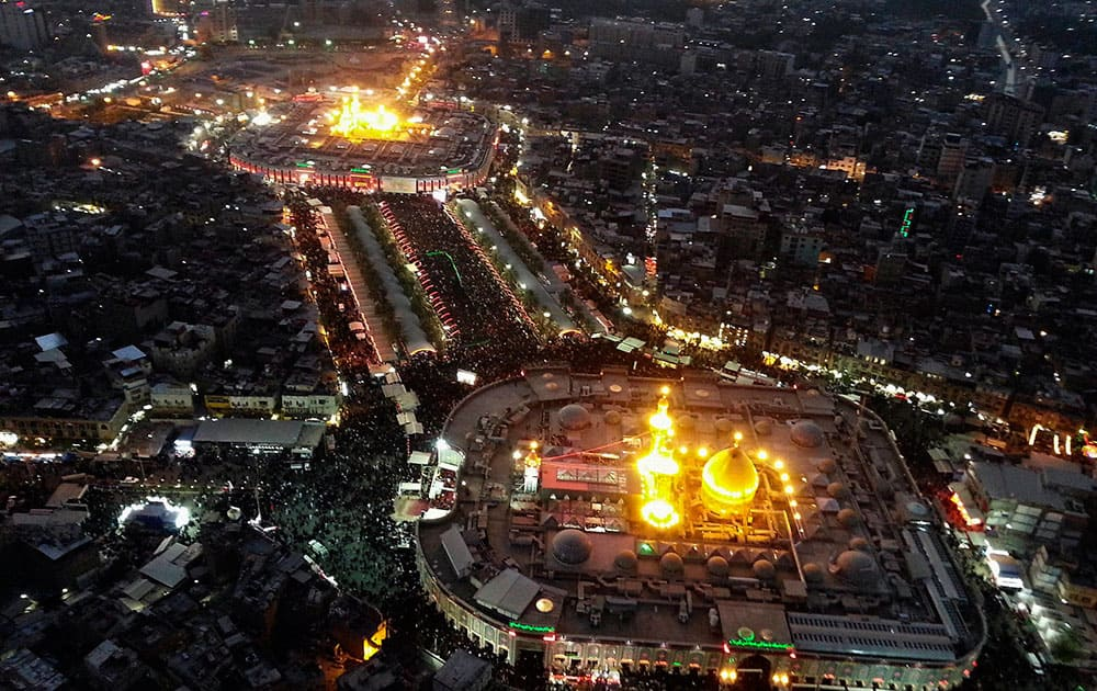 This aerial photo shows Shiite faithful pilgrims gathering between the holy shrine of Imam Hussein, top, and the holy shrine of Imam Abbas, bottom, during the Muslim month of Muharram