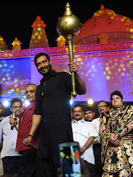 Actor Ajay Devgn holds a mace during Dussehra celebrations of Luv Kush Ramlila Committee Committee at Red Fort in New Delhi