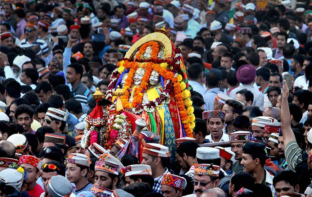 Devotees carrying idol in a procession taken out on the occasion of International festival of Kullu Dussehra in Kullu
