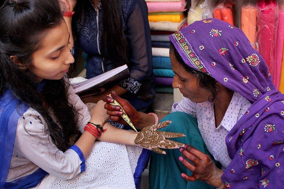 Women get mehndi (henna) designs on their palms ahead of Karva Chauth