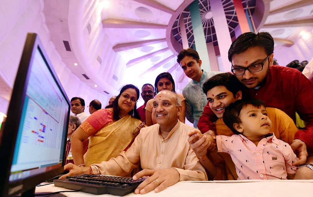 """A stockbroker trades as his family watches during a special """"muhurat"""" trading session for Diwali at BSE in Mumbai"""