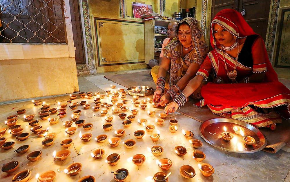 Women light earthen lamps Diyas at Ramchandran Ji temple on the occasion of Diwali Festival in Jaipur
