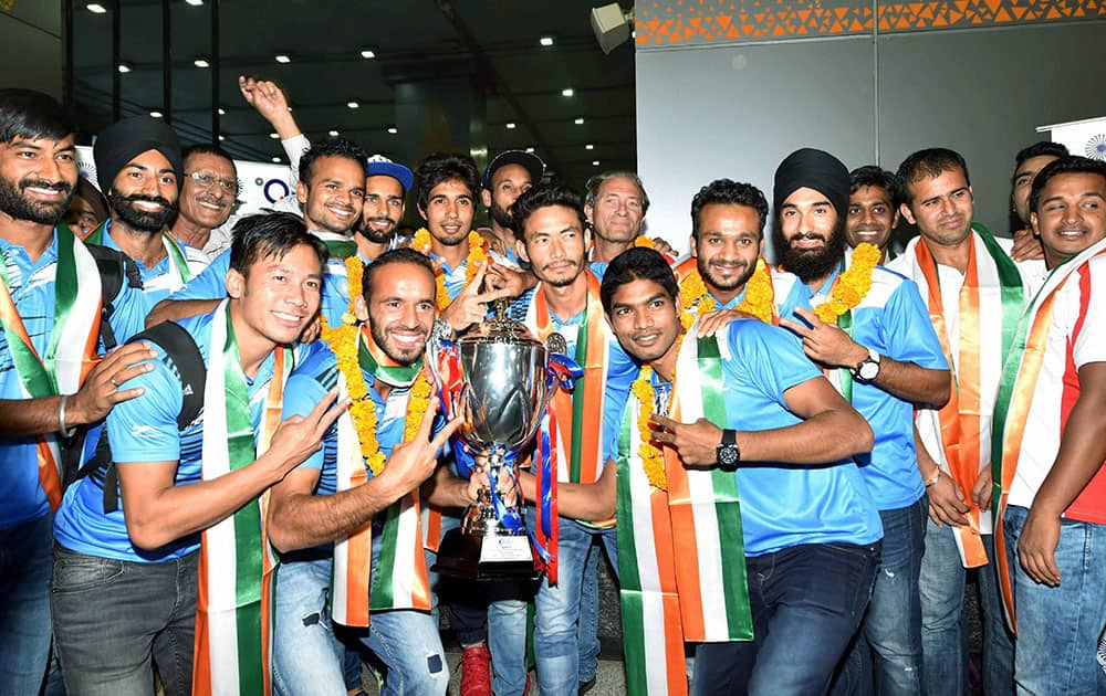 Hockey player Sardar Singh pose with the Asian Champions Trophy as they arrives at T3 terminal in New Delhi
