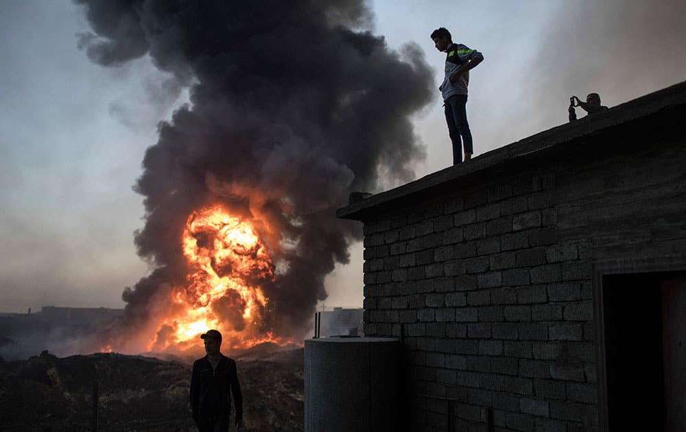 People watch as safety workers try to extinguish fire from a burning oil field in Qayara,
