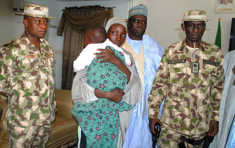Nigerian troops stand next to a recently rescued Nigerian Chibok girl