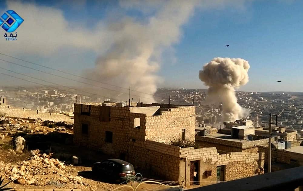 a plume of smoke rises after a missile falls on the town of Darat Izza, Aleppo, Syria
