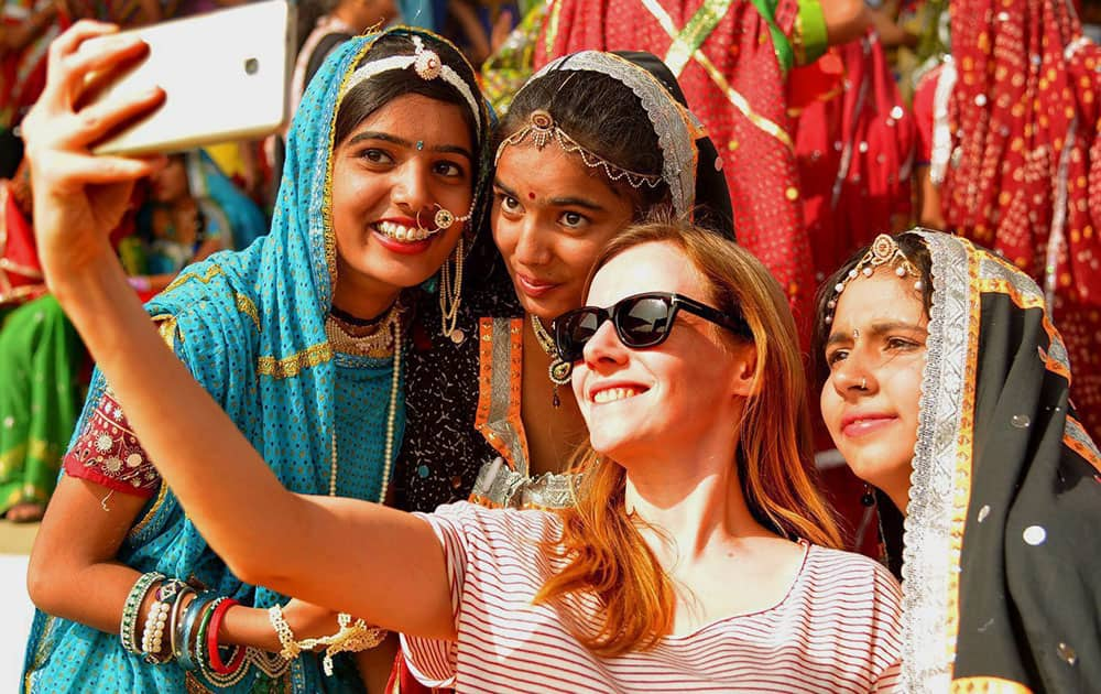 A foreign tourist takes selfies with Indian artists at Pushkar Camel Fair in Pushkar