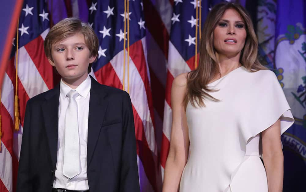 Barron Trump and his mother Melania Trump stand on stage