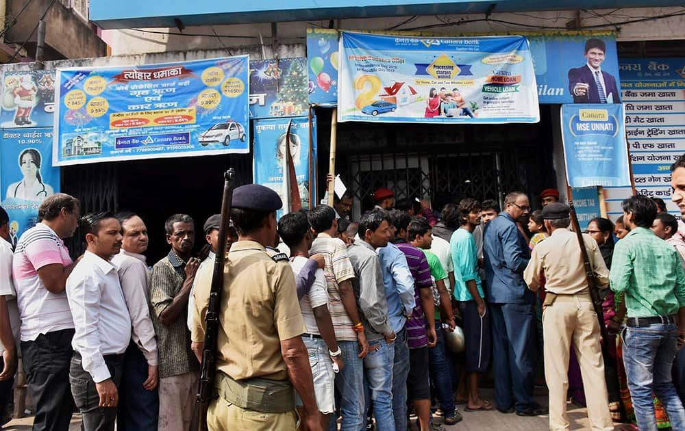 Police control the crowd of people queue up at a bank for exchanging their old Rs 1000 and Rs 500 notes in Patna