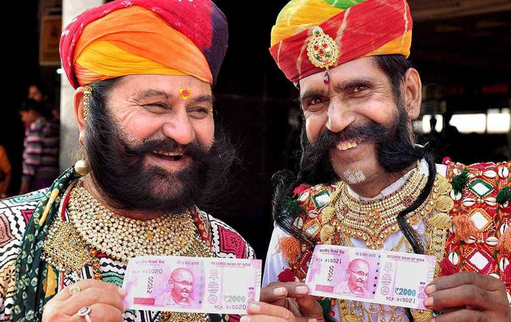Rajasthani artists showing Rs 2000 notes after exchanging their old notes in Bikaner