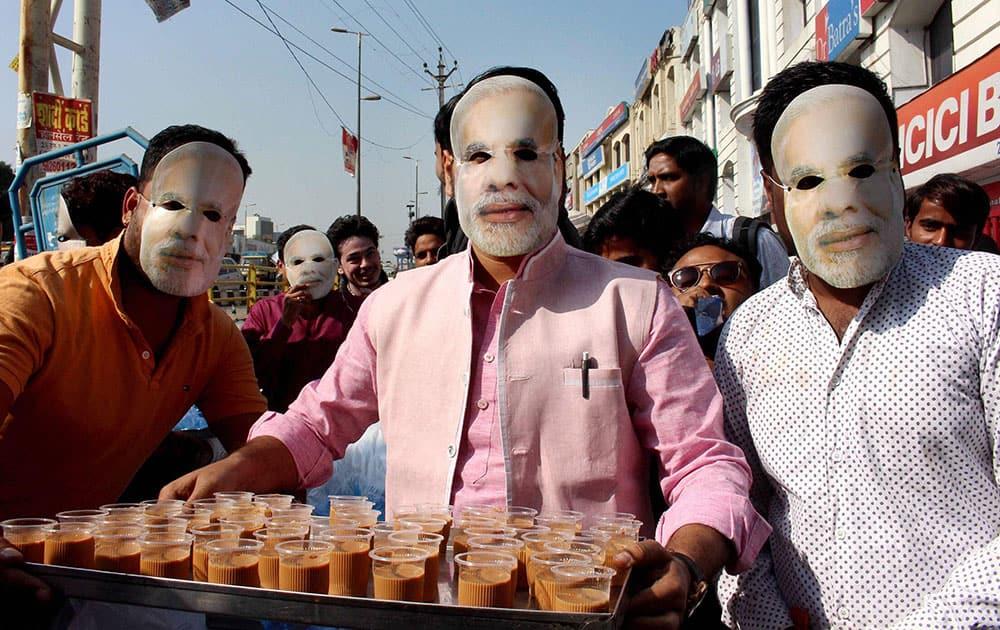 BJYM workers wearing masks of Prime Minister Narendra Modi serve tea