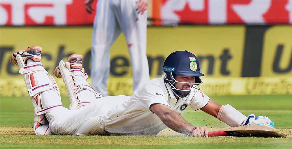 Cheteshwar Pujara dives to complete a run during the 1st day of the 2nd Test cricket match against England in Visakhapatnam