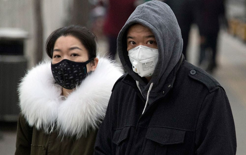 A man and woman wear masks as they walk on a street in Beijin
