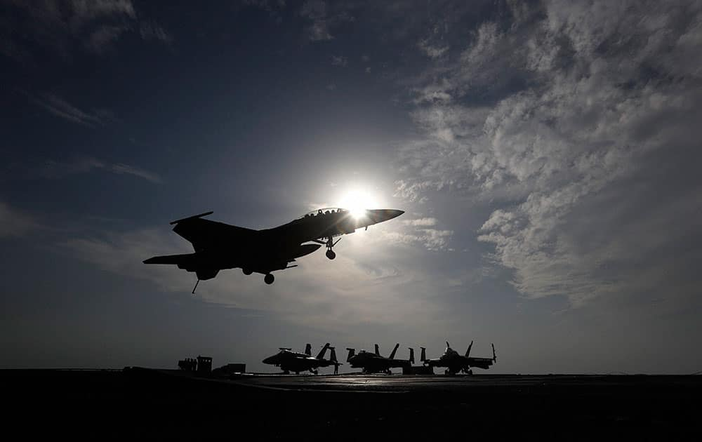 A U.S. Navy fighter jet lands on the deck of the U.S.S. Theodore Roosevelt aircraft carrier