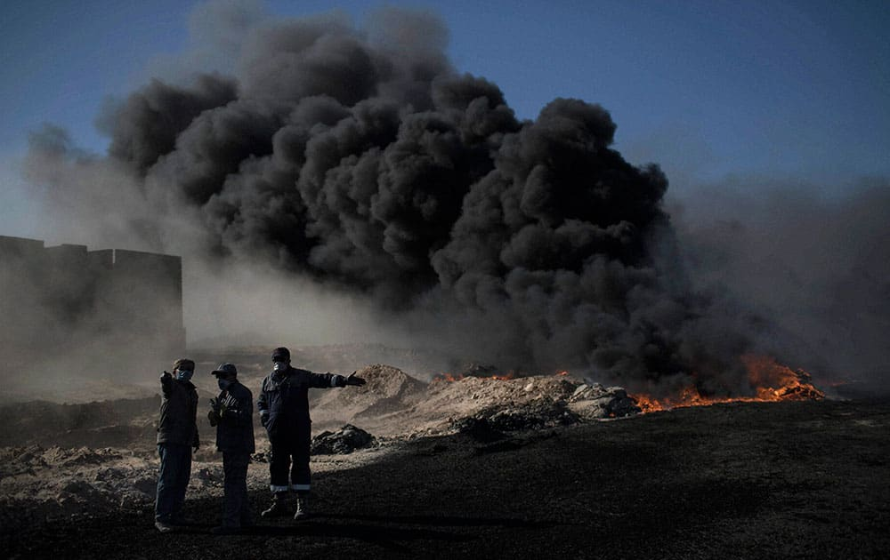 Oil workers try to extinguish burning oil fields in Qayara, south of Mosul