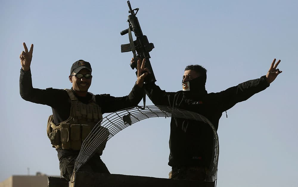 raqi special forces soldiers flash victory signs
