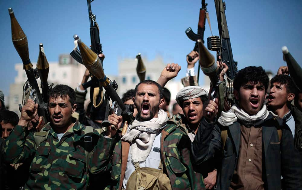 Tribesmen loyal to Houthi rebels hold their weapons