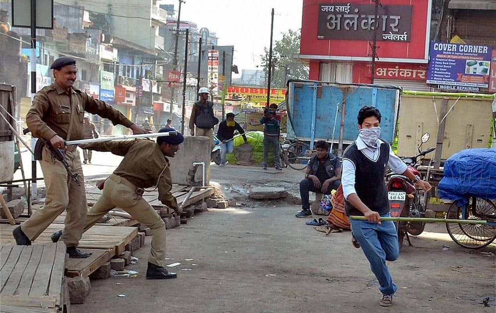 Police chase away one of the protesters who were out on a street for enforcing Jharkhand bandh