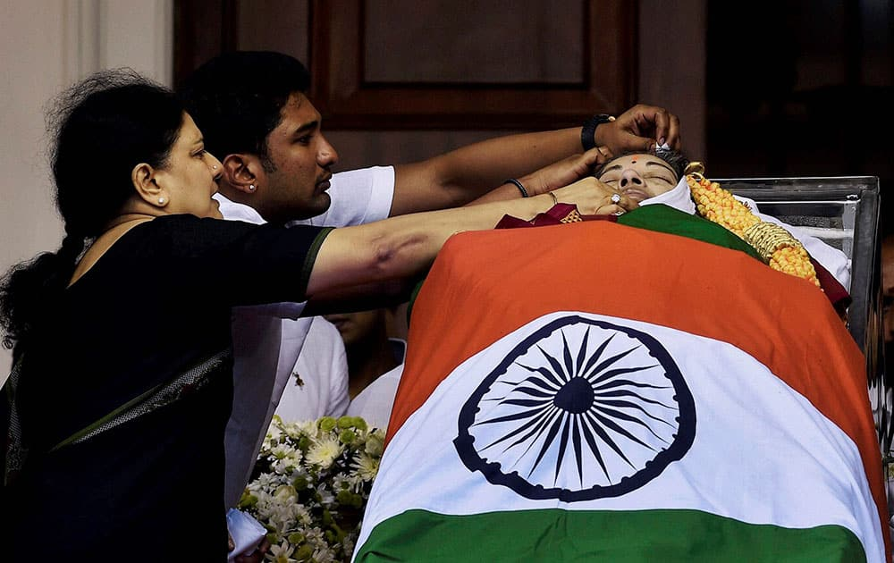 V Sasikala, the close aide of Tamil Nadus former Chief Minister Jayaram Jayalalithaa adjusts a cloth around her mortal remains