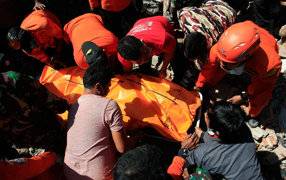 Rescue workers pull victims from destroyed buildings in Sigli, Aceh Province, Indonesia