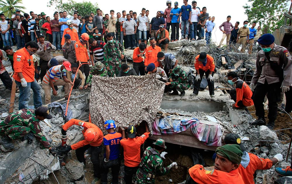 Indonesian army and the Search and Rescue Team look for survivors amongst the rubble in Lueng Putu town, Aceh Province, Indonesia
