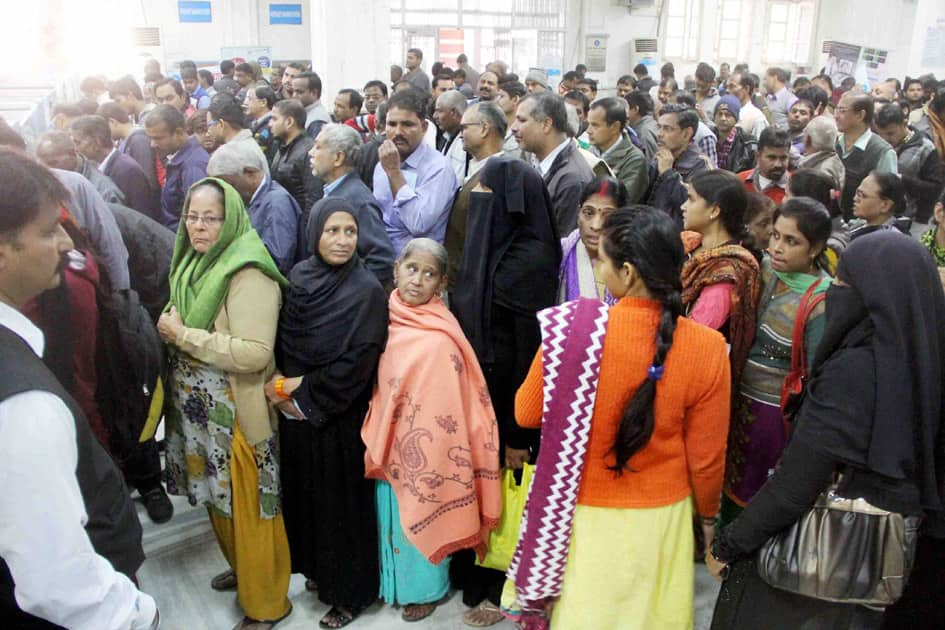 People stand in long queues to withdraw cash