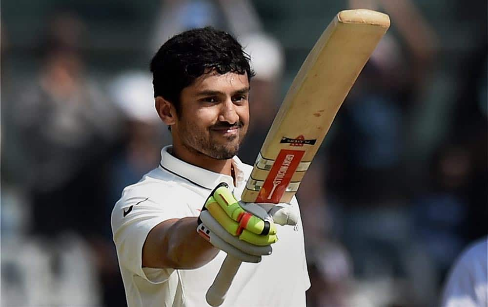 Karun Nair raises his bat after scoring his maiden century in an international match