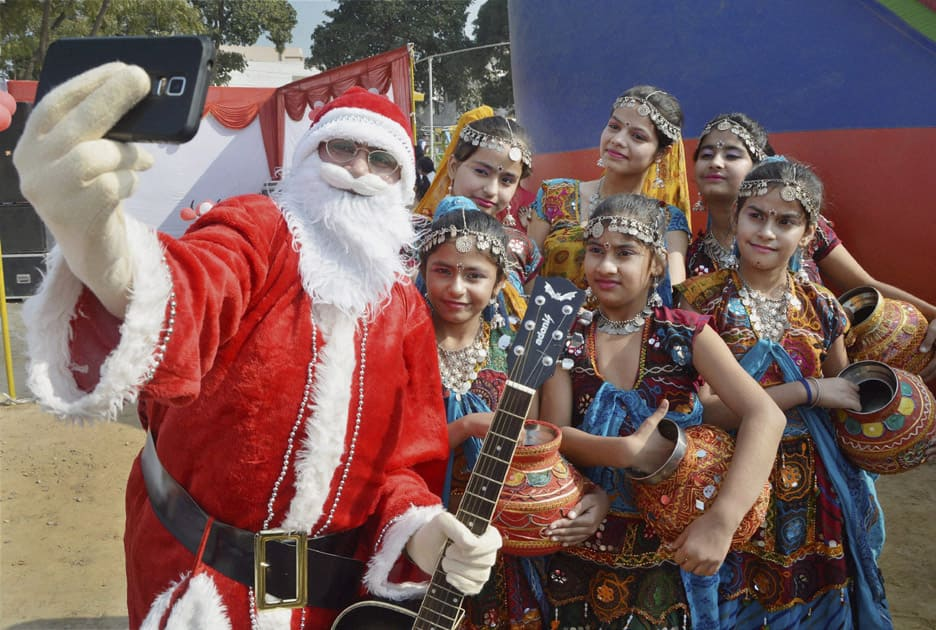 Santa Claus takes a selfie with children