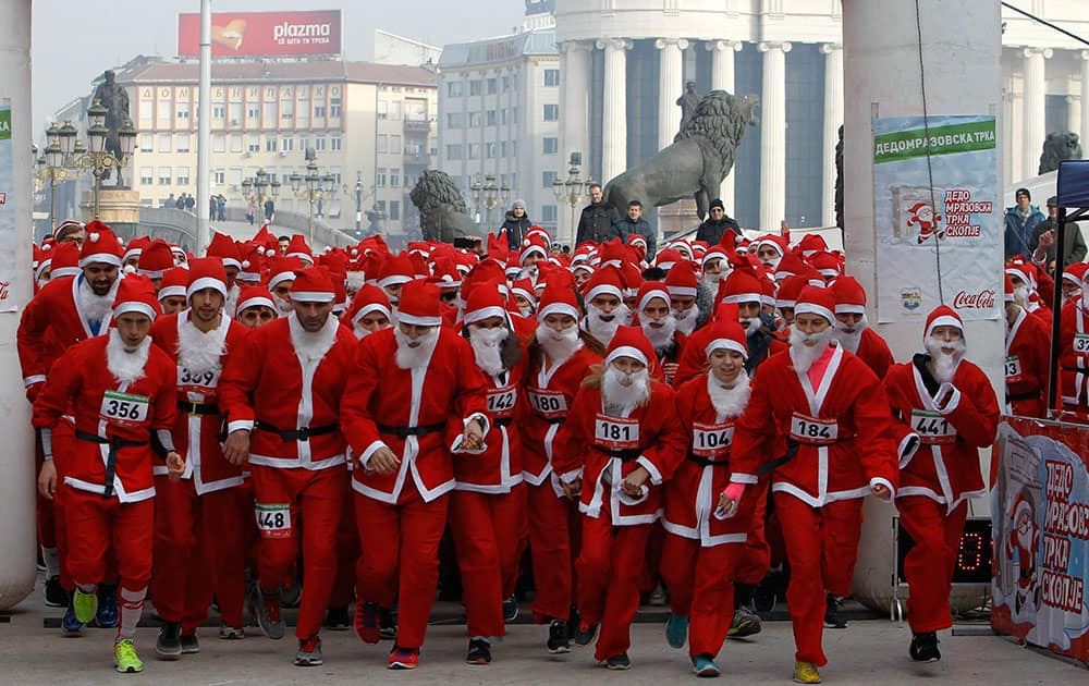 People dressed in Santa Claus costumes run at the start of a Santa Claus Race