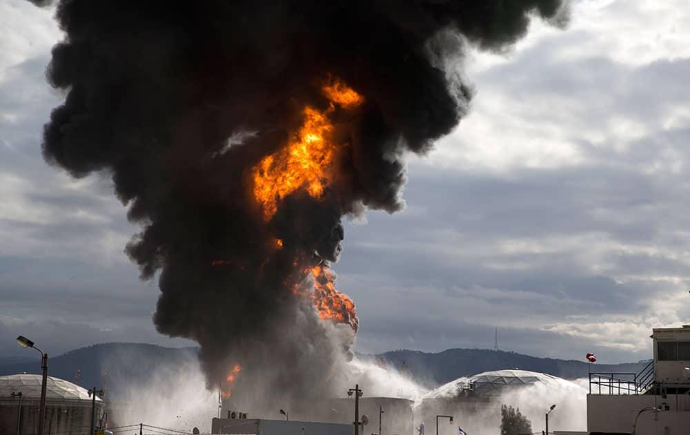 Fire fighters fight flames in a fuel tank in Oil Refineries Ltd