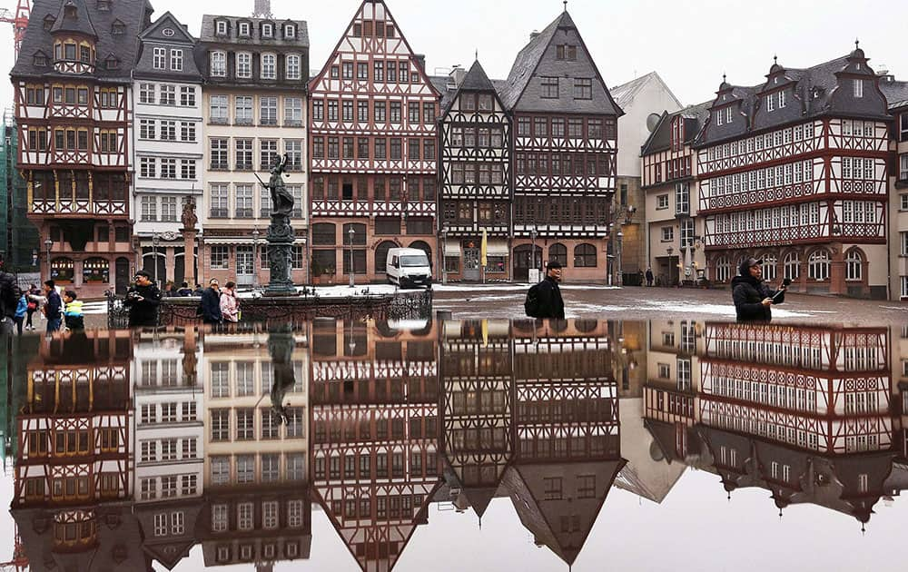 The timber-frame houses at the Roemerberg square are reflected in water