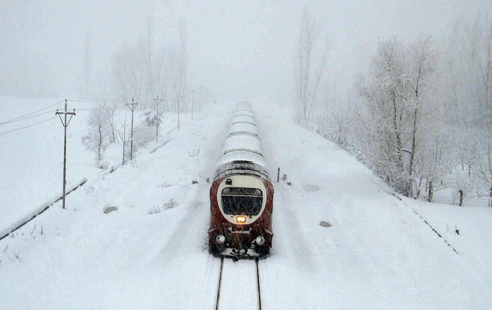 Train moves on snow covered Srinagar-Qazigund rail track
