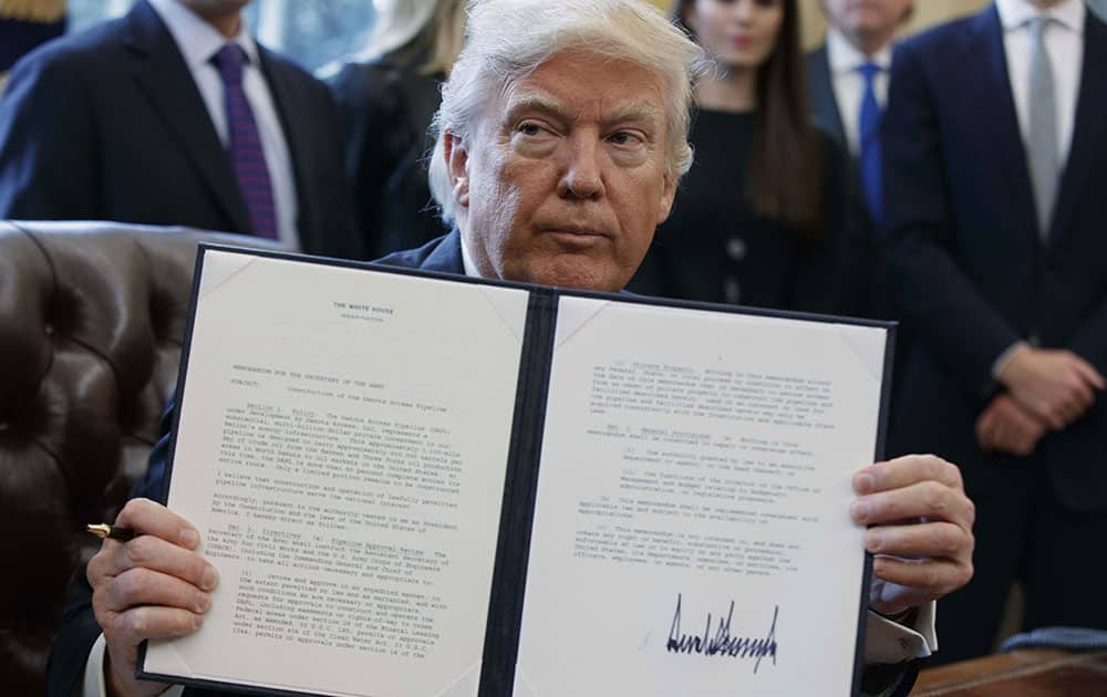 President Donald Trump shows off his signature on an executive order