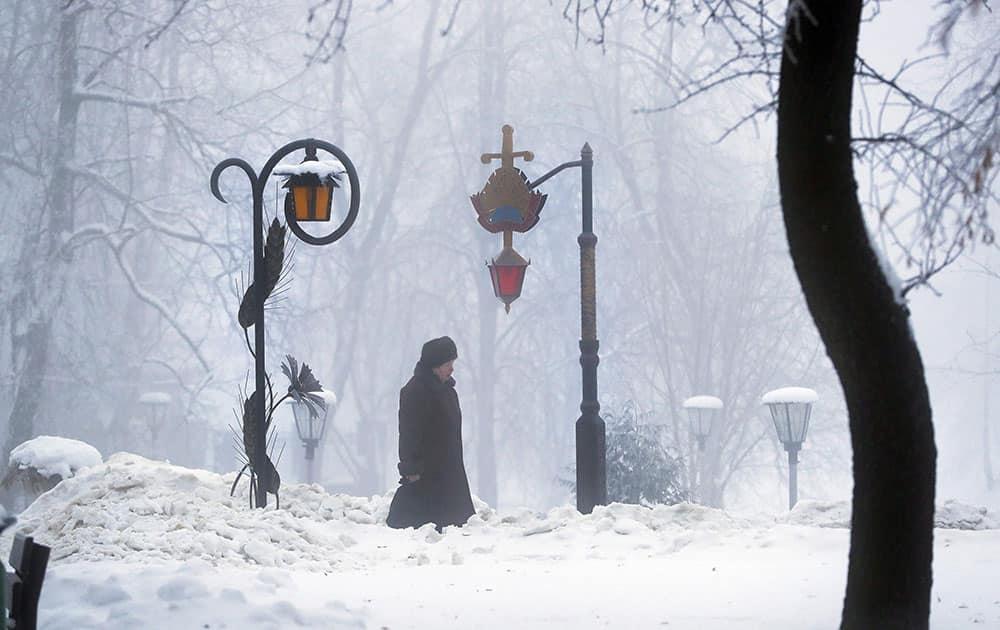 A woman walks through a snowy park in Minsk